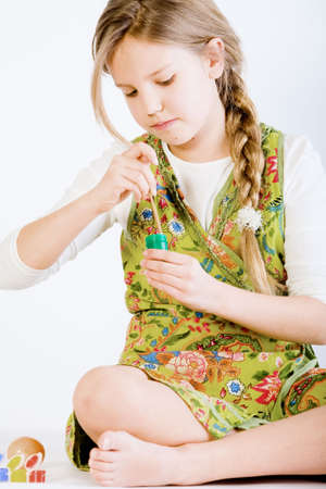 creative egg painting: Studio portrait of a young blond girl who is painting
