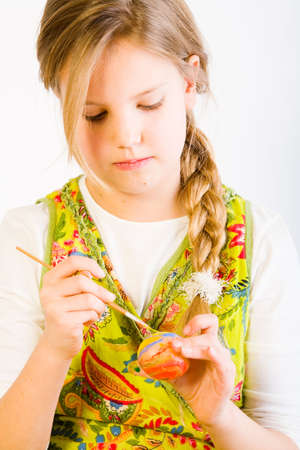 Studio portrait of a young blond girl who is painting eggs for easter Stock Photo - 2369232