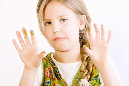 Studio portrait of a young blond girl showing her hands smudged with paint Stock Photo - 2369210