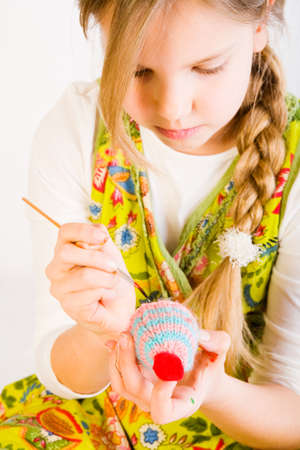 Studio portrait of a young blond girl who is painting eggs for easter Stock Photo - 2369225