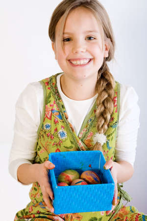 Studio portrait of a young blond girl who is presenting a blue box with her painted easter eggs photo