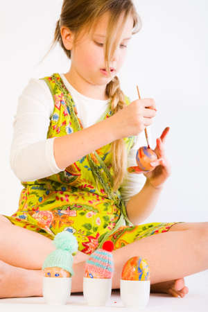Studio portrait of a young blond girl who is painting easter eggs photo