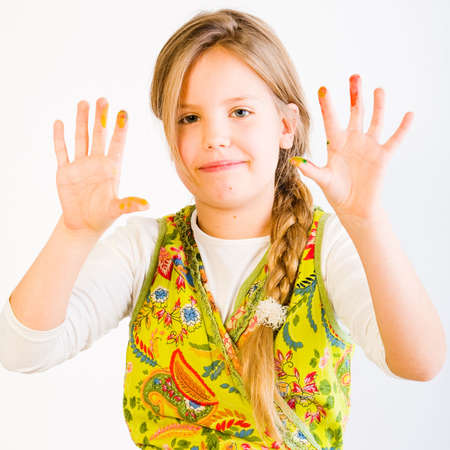 studioshot: Studio portrait of a young blond girl showing her hands smudged with paint