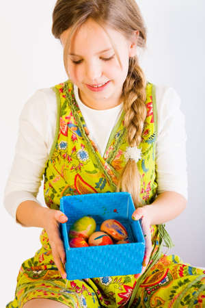 Studio portrait of a young blond girl who is shwong a box full of easter eggs photo