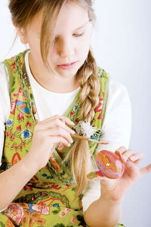 Studio portrait of a young blond girl who is painting eggs for oyster photo