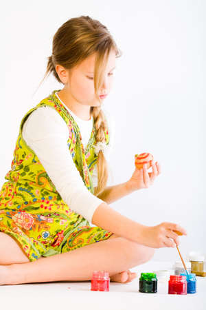 Studio portrait of a young blond girl painting eggs for easter photo