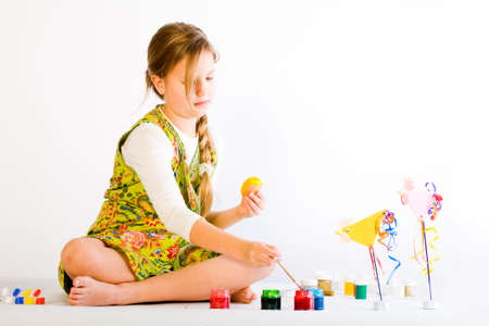 Studio portrait of a young blond girl who is painting easter eggs Stock Photo - 2369213