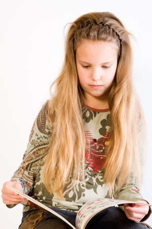 long straight hair: Studio portrait of a blond child reading a book Stock Photo
