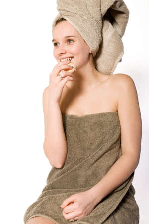 studioshot: Young woman in towel on a white background eating Stock Photo