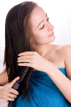wet woman: Woman is brushing her hair in the studio