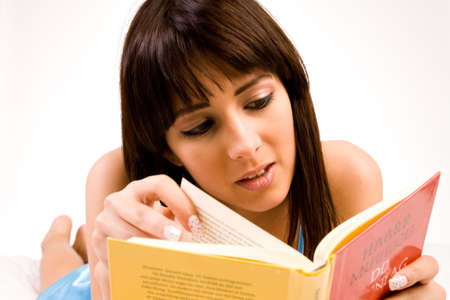 Brunette in pyjamas reading a book in bed. Titles have been made unreadable so no copyright infrigment. photo