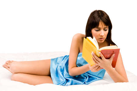 unreadable: Brunette in pyjamas reading a book in bed. Titles have been made unreadable so no copyright infrigment. Stock Photo