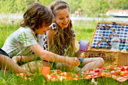 Twee kinderen genieten van een picknick in de zomer Stockfoto