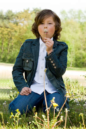 young boy is blowing a flower in the wind
