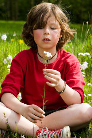 young boy is looking to his flower photo