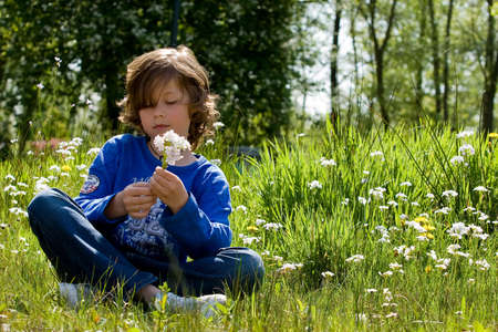 young boy is sitting in the grass photo