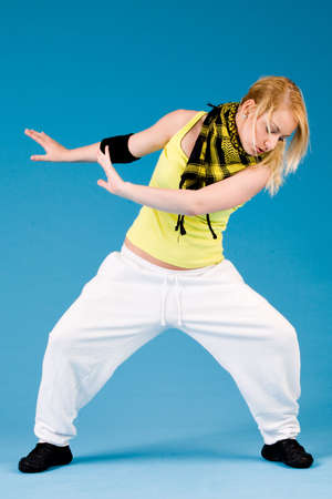 Attractive blond girl is dancing on a blue background