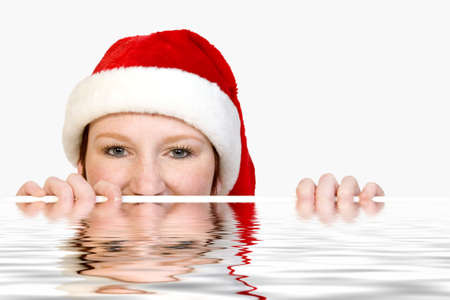 Portrait of a cute christmas fearie who is looking over the edge of a pool. photo