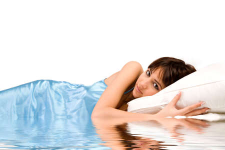 Cute girl in bed hugging her pillow on water photo