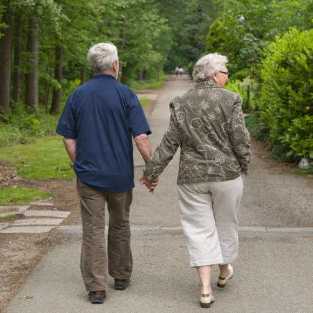 outside portrait of an elderly couple walking along a forest road photo