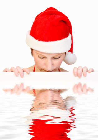 Beautiful girl in christmas bikini and with christmas hat is holding up a white sign for copy space. With background clipping path for your convenience photo