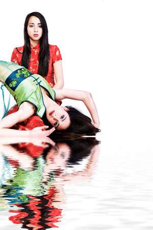 Studio portrait of two beautiful mixed race vietnamese sisters photo