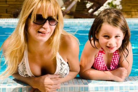 Young blond girl and her sister enjoying the sun in and around the swimming pool Stock Photo