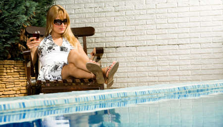 Young blond girl enjoying the sun in and around the swimming pool photo