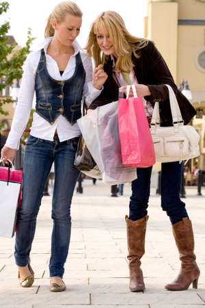 Two young girls shopping in the sunny weather Stock Photo - 3688192