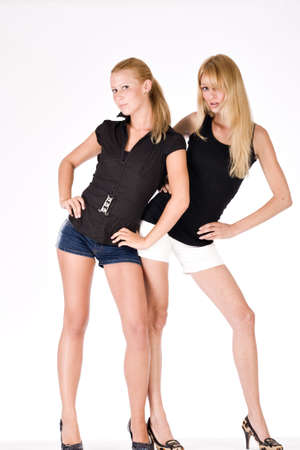 Two sisters in shorts striking a fashion pose photo