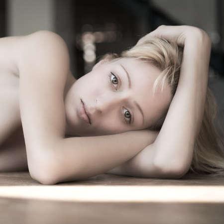 Portrait of a young girl lying on the floor feeling sad.