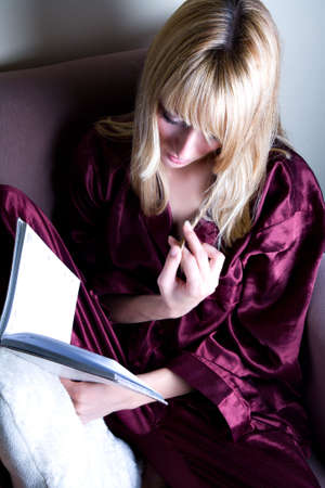 lookalike: Paris Hilton look-a-like is playing her hair while reading a book