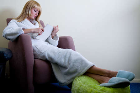 lookalike: Blond model in bathrobe and slippers who looks like Paris Hilton is reading a book