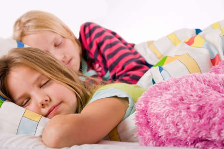 Two young children enjoying their colorful bed