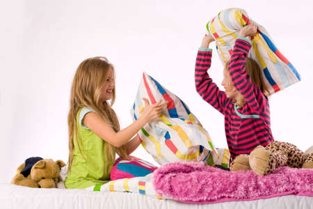 pillow fight: Two young children enjoying their colorful bed