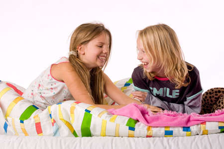 Two young children enjoying their colorful bed Stock Photo - 3760650