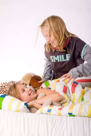 Two young children enjoying their colorful bed Stock Photo - 3766967