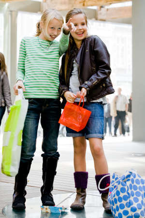 Two yuong children hanging around the streets while shopping