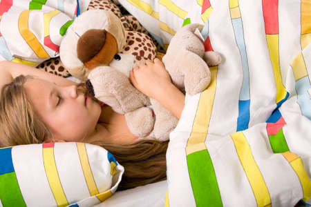 Sleeping young cute child in a colorful bed
