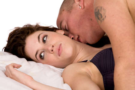 A young couple being together in bed photo