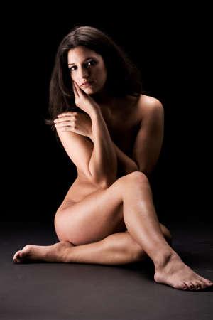 Portrait of a nude brunette in a low key setting