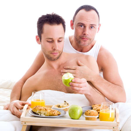 A Happy homo couple and their breakfast on a tray in bed photo