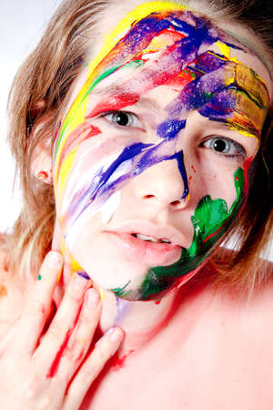 aggresive: Studio portrait of a teenage girl painting herself