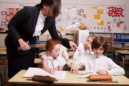 Group of little students with different ages in a classroom Stock Photo