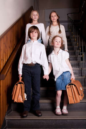 Group of little students with different ageson the stairs photo