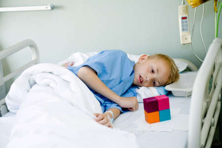 Portrait of a sick young boy after an operation in his hospital bed. photo