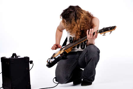 hardrock: Young girl adjusting her guitar and amplifier Stock Photo