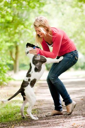 mujer con perro: Chica rubia y un bulldog americano en el parque Foto de archivo
