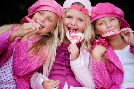 gemelas: Felices los ni�os tengan ropa de color rosa y un lollipop Foto de archivo