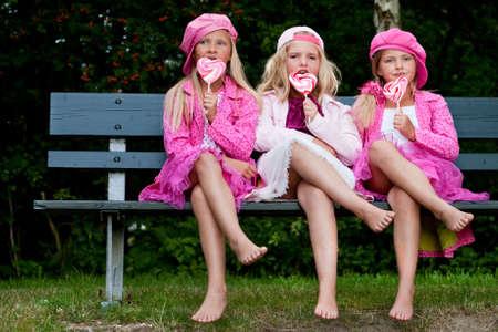 paletas de caramelo: Felices los ni�os tengan ropa de color rosa y un lollipop Foto de archivo
